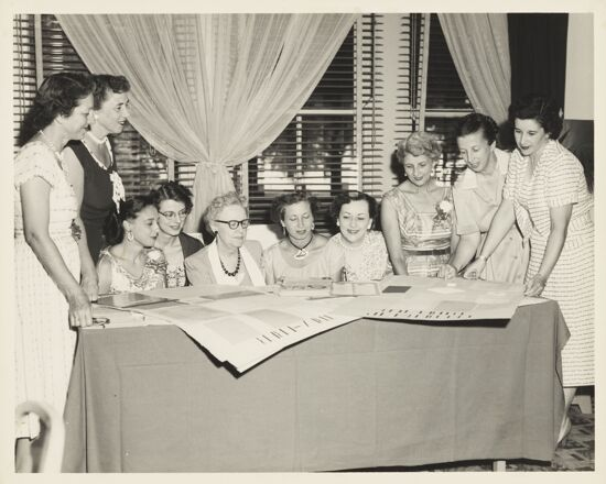 Edgewater Convention Group Looking at Posters Photograph, 1956 (image)